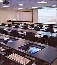Computer classroom with monitor screens inserted at an angle in the desktops with smartboard at the front of the classroom