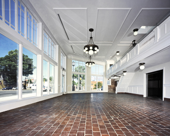 Interior of a former auto showroom showing the mezzanine with brick flooring, white painted woodwork, detailed celing with white globe chandeliers