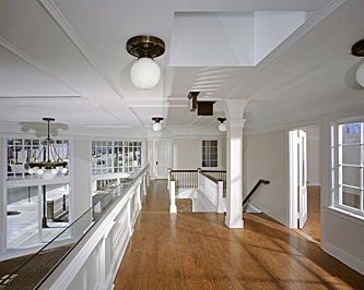 Upstairs interior of a former auto showroom showing hardwood flooring, white painted woodwork, detailed celing with white globe chandeliers, and a view down to the mezzanine