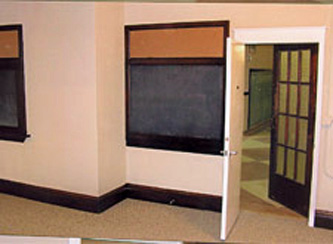 Interior View: Retention of glass doors along historic corridor by incorporating new, code compliant doors on the interior.