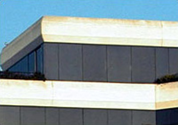 top floors of the exterior of an angular building with white trim yellowing from lack of upkeep and tinted windows