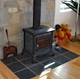 An efficient black wood burning stove in the living room of a new home