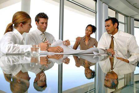 Four people sitting around a glass conference table looking over plans