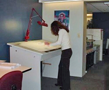 woman using a standing workstation in her workplace