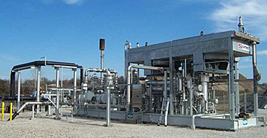 Photo that shows a landfill gas treatment station with a blower and flare.