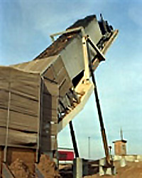 Image of a generation station with a large skip of woody materials from the agricultural industry being loaded into it.