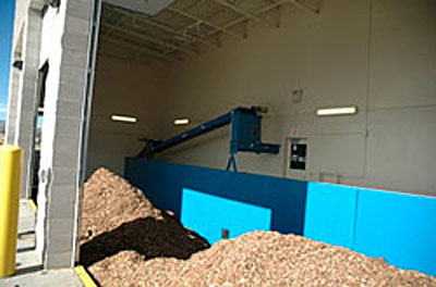Photo showing piles of wood chips in the wood chip storage area at the Boulder County Parks and Open Space campus district heating system