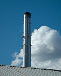 Photo of an exhaust stack on a biomass system on the roof of a California greenhouse