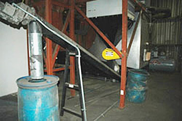Photo of an automated ash-removal system on a wood-fire boiler. The boiler is located in the lower right portion of the photo, and the system uses an auger to remove ash from the boiler. It then delivers the ash to a blue barrel located on the left of the photo.