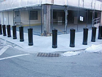 bollards on along a sidewalk and around a corner with a grate on the road in front and some snow on the ground and a new construction building behind