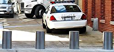 four steel active electric bollards outside a police station