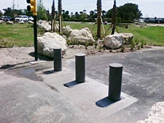 three retractable bollards at a stoplight with large rocks on the left side of the roadway