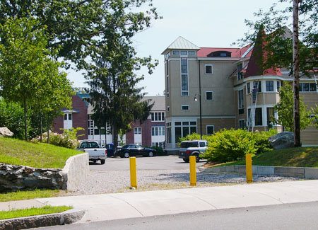 Image of Lasell College in Newton, MA with three yellow bollards at the entrance