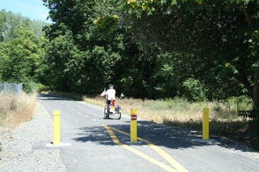 man on a bicycle moving away from three bollards along the American River Trail in Redding, CA