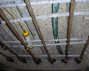 Discrete zinc anode (wrapped in green mesh) in concrete deck repair. The device with the yellow lead wire is a permanent reference electrode.