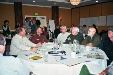 Charrette work groups work at round tables in a large meeting room-note the flip chart pages taped to the walls.