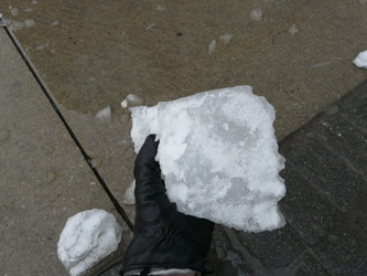 A gloved hand holding a chunk of fallen ice