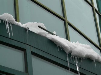 Detail of the side of a building with ice pushing out a piece of barrier trim