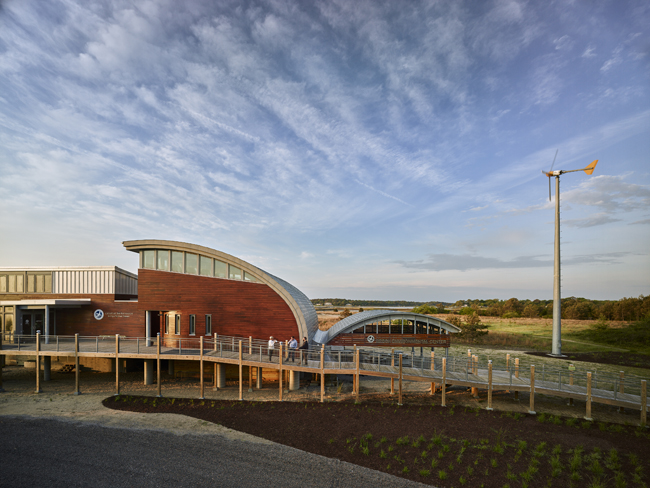 Exterior of the Brock Environmental Center with view of the elevated entry ramp, and roof forms resembling gull wings that allow for rainwater collection.