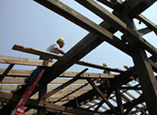 Worker deconstructing a wooden structure