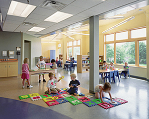 Young children playing on floor mats and at tables in a well-lit, window-filled child development center