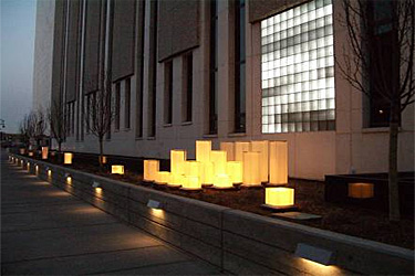 Sidewalk view of building at night with lights embedded in short wall illuminating the sidewalk and array of decorative lights in front of glass block facade