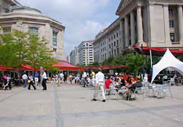 plaza space between office buildings featuring vendors under awnings, wide spaces for pedestrians, and tables and chairs for seating