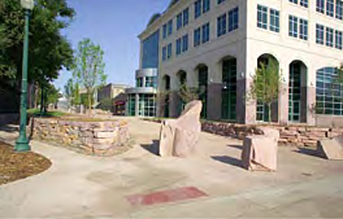 Public plaza created between buildings featuring stone bollards and stone walls