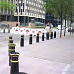Street setting with a row of decorative black bollards with white trim mounted on concrete sidewalk