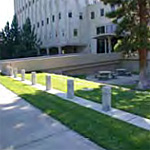Plain concrete style bollards mounded on a contrete strip placed in the grass between the sidewalk and federal building