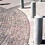 Plain bollards mounted in concrete forming a curve adjacent to a highly decorative curved paver design