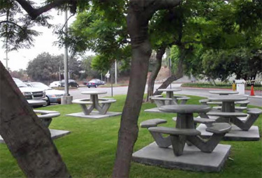 Small park next to an office parking lot in and gated entrance featuring all in one picnic tables.