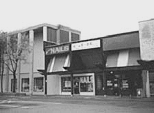 B/W photograph of a sidewalk and storefronts