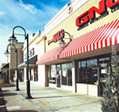 Storefronts like GNC along the sidewalk