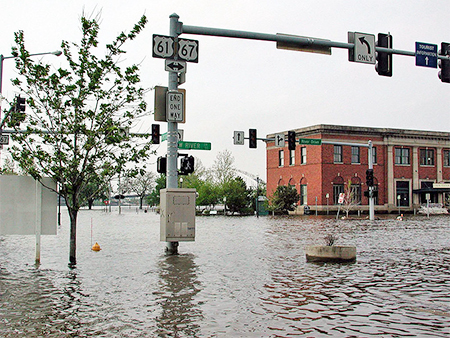 Photo of Mississippi River flooding a downtown with water levels high on a stoplight