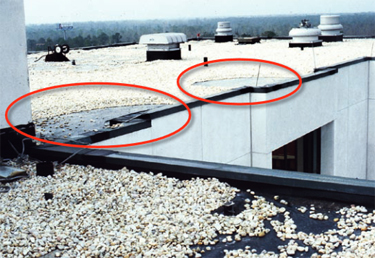 Photo of a single-ply membrane roof where the aggregate ballast was blown away in the vicinity of the corners of the wall projections at the window bays