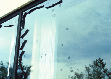 Exterior glazing damage, the outer panes of these windows were broken by aggregate from a built-up roof