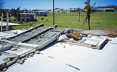 Photo of a waffled precast concrete roof deck where portions were blown off because anchor plates and nuts had not been installed