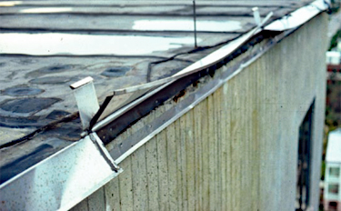 Vertical flange on metal flashing disengaged and lifting up