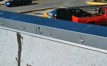 Use of exposed fasteners to attach vertical flanges of coping and edge flashing