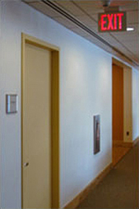 photo of a hallway with an opening a closed door with an exit sign