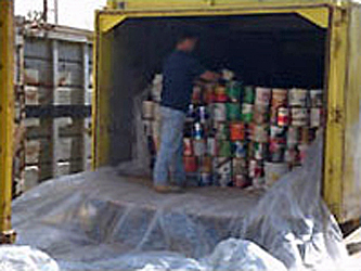 Photo of a man stacking latex paint cans into the back of truck for recycling
