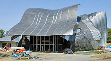 Photo 7 showing building with curved roof composed of multiple metal components