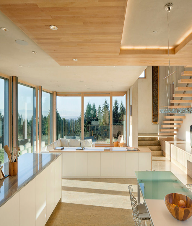 interior of the Karuna House, Porland Oregon facing out from the kitchen with views of the staircase, living room and outdoor views