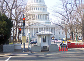 In front of the US Capitol building the guard house is shown next to a red stoplight with concrete planters (without plants) and pre-cast concrete drainage structure rings as barrier protection