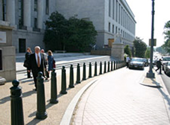 A line of bollards separating a pedestrian sidewalk with a drop-off area and the roadway