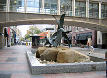 A low walled box along a curb to restrict vehicles featuring large stones and a bronze sculpture