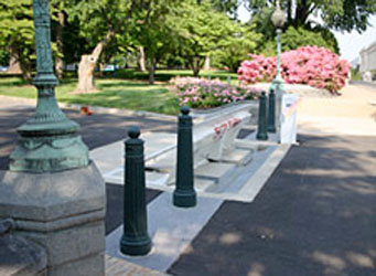 Rising plate vehicle barriers in the center flanked by decorative bollards