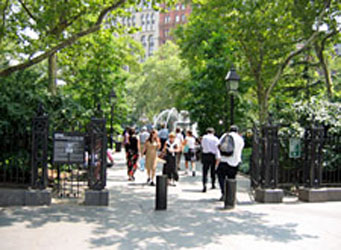 An open entry gate with pedestrians walking along a path between trees set in low walls and among bollards
