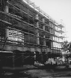 black and white photograph of a building beng renovated with all the outside walls removed